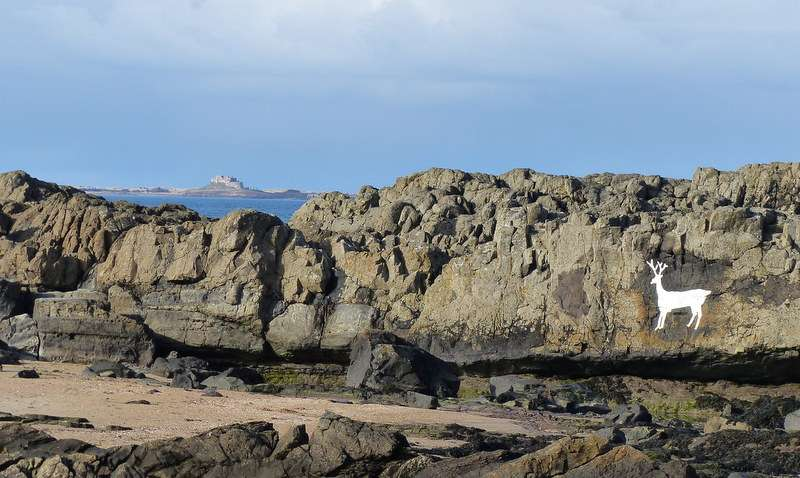 The Stag Rock pool on Bamburgh beach, Lindisfarne Castle in the distance.